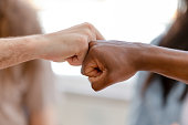 Diverse male hands giving fist bump, close up view