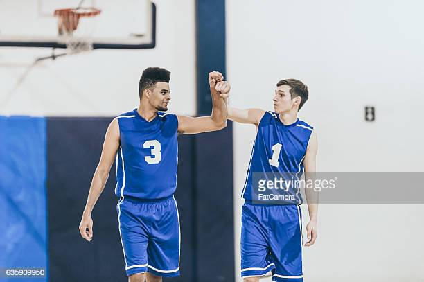 Diverse male high school teammates high fiving during game
