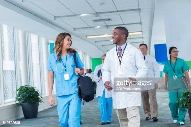 Diverse medizinische Fachkräfte sprechen im Krankenhaus Flur miteinander.