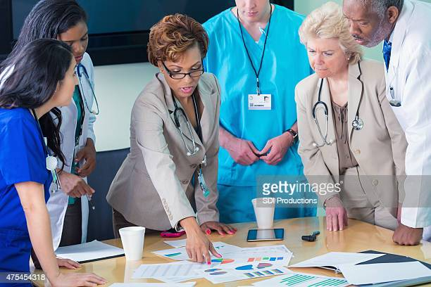 diverse medical team or board reviewing hospital financial information - administrator stock pictures, royalty-free photos & images