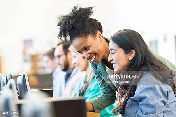 Diverse mid adult students using computers during class in college