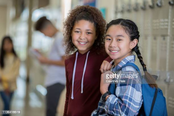 diverse middle school girls smiling at camera in hallway near lockers before class - children only stock pictures, royalty-free photos & images
