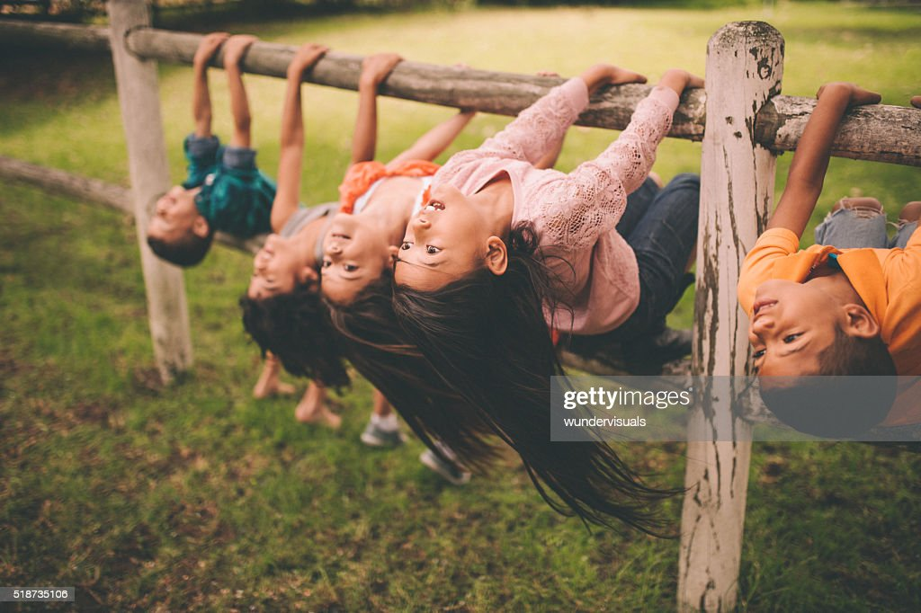 Diverse mixed racial group of children on fence in park : Stock Photo