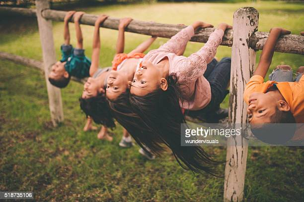 diverse mixed racial group of children on fence in park - funny black girl stock photos and pictures