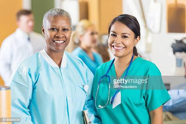 Diverse nurses smiling in busy hopsital blood bank