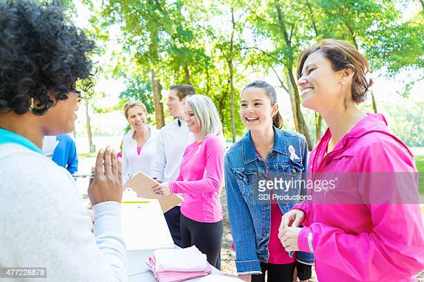 Diverse people registering for breast cancer awareness charity race
