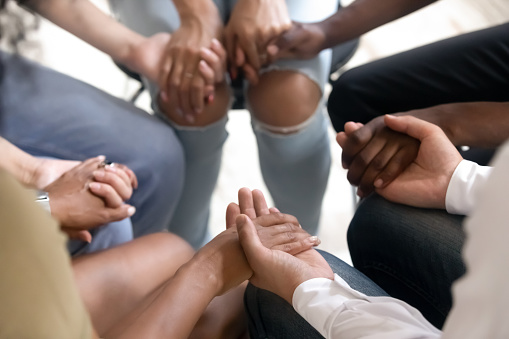 Diverse people sitting in circle holding hands at group therapy 1139791216