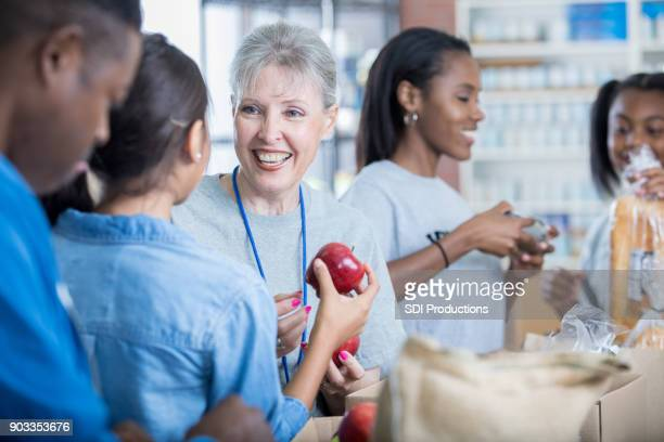 diverse people volunteer at food bank - food bank stock pictures, royalty-free photos & images