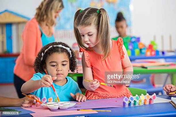 Diverse preschool friends enjoy painting together