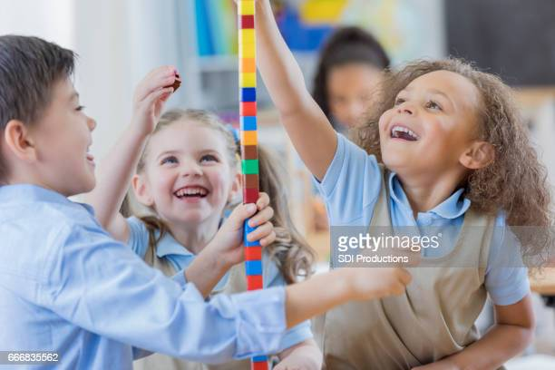 Diverse preschool friends play with counting cubes