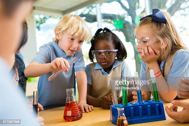 Diverse private elementary school students doing science experiment