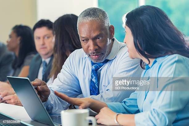 Diverse professionals studying financial information in conference or seminar