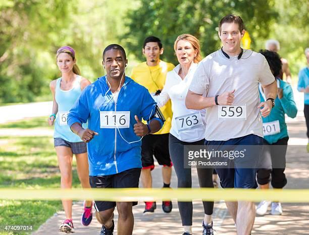 Verschiedene Läufer nähern Ziellinie während des Marathons im park