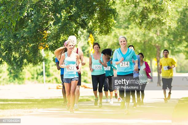 diverse runners approaching finish line during marathon or 5k race - charity benefit stock pictures, royalty-free photos & images