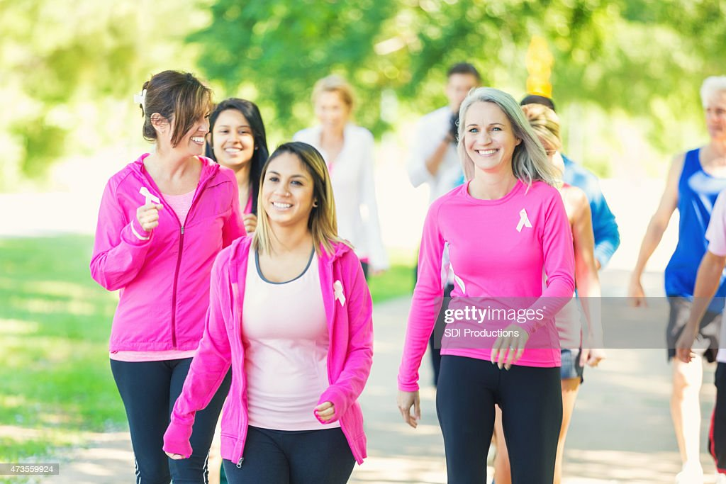 Diverse runners participating in breast cancer awareness race : Stock Photo