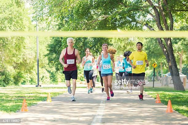 Divers coureurs de cours'avec passion en direction de ligne d'arrivée du marathon