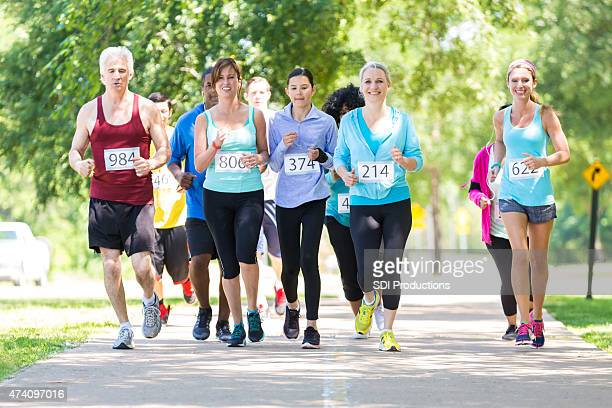 diverse running team approaching finish line during marathon - charity benefit stock pictures, royalty-free photos & images