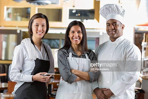 Diverse staff in modern open kitchen restaurant dining room