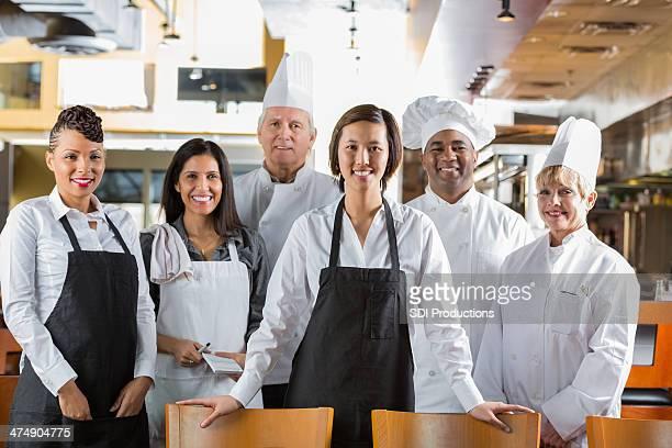 Diverse staff of chefs and waiters in modern restaurant kitchen