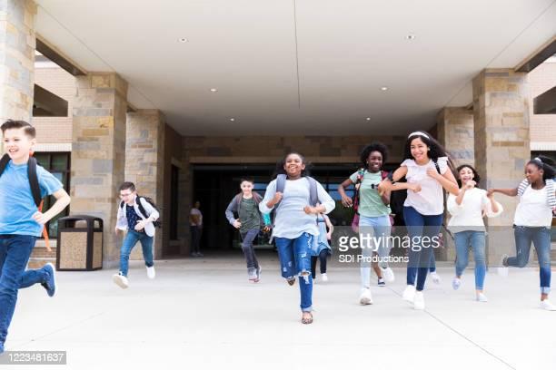 diverse schüler rasen nach der schule in richtung bus - staatliche schule stock-fotos und bilder