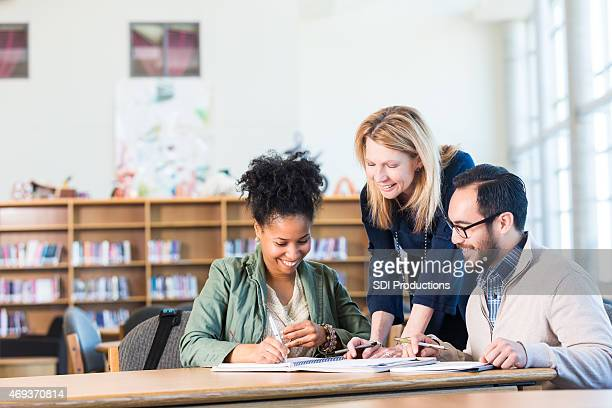 Diverse study group of adults working in large college library