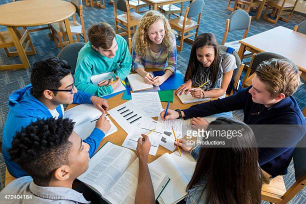 Diverse study group of teenagers studying together in library