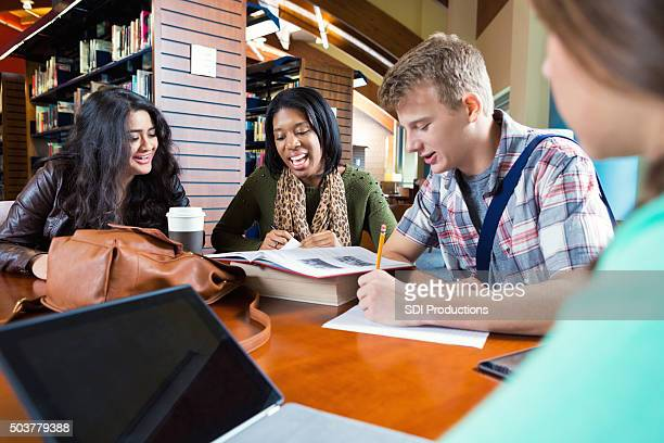 Diverse study group working on class assignment in library