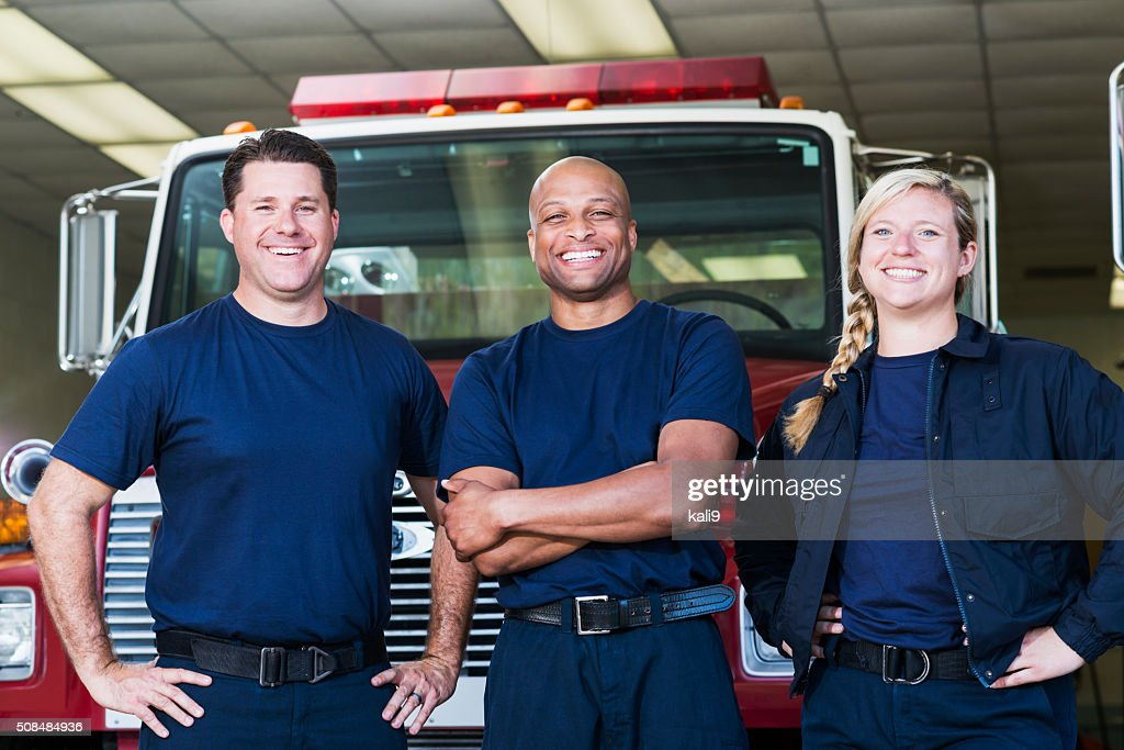 Diverse team of firefighters in front of fire engine : Stock Photo