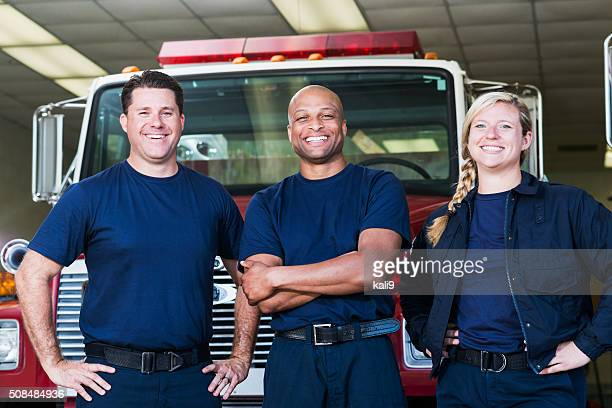 diverse team of firefighters in front of fire engine - firefighter stock pictures, royalty-free photos & images