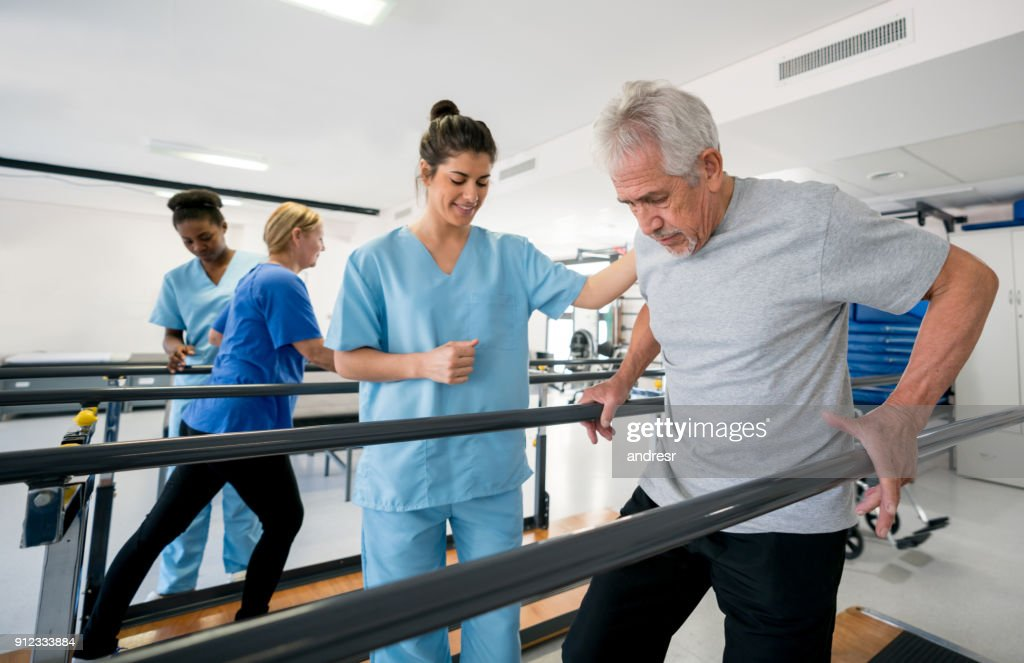 Diverse team of physiotherapist helping patients walk between parallel bars : Stock Photo