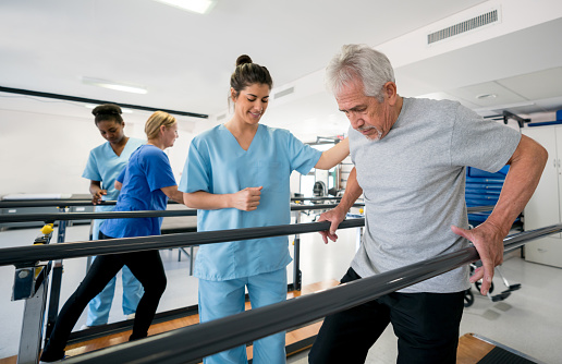 Diverse team of physiotherapist helping patients walk between parallel bars 912333884