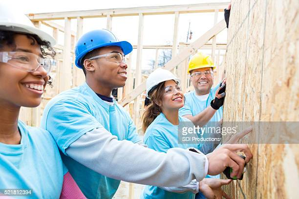 Diverse team of volunteers build wall in charity home