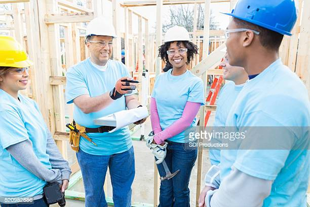 Diverse team of volunteers discuss charity building project