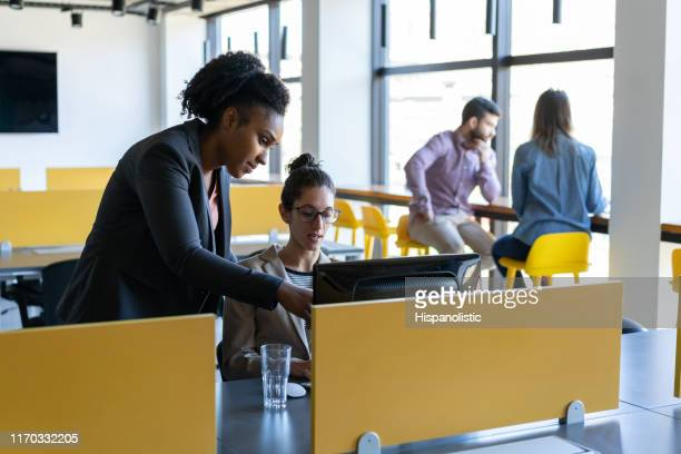 Diverse team of women working on a project together discussing something while looking at screen very focused
