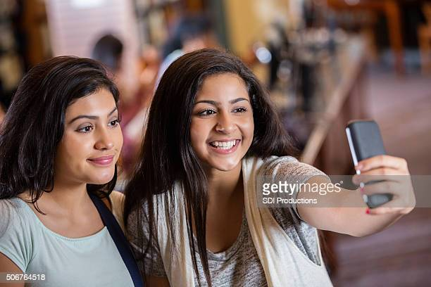 diverse teen girls taking selfie photo with phone in library - indian college girls stock photos and pictures