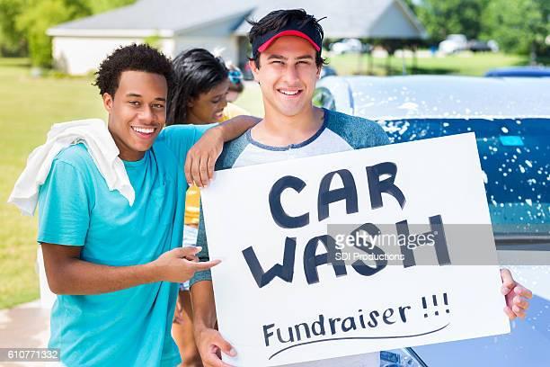Diverse teenage boys hold 'Car Wash' fundraiser sign