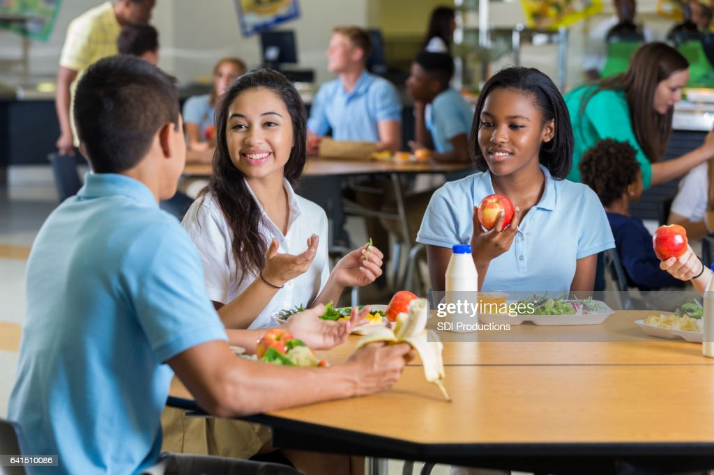 Diverse teenage friends eat lunch in school cafeteria : Stock Photo