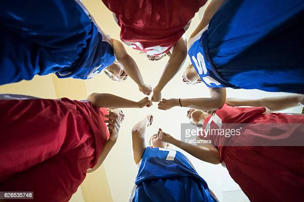 diverse teenage girl athletes cheering after their team huddle - basketball sport stock photos and pictures