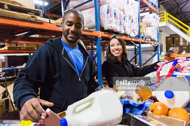 Diverse Volunteers cheerfully sorting food items