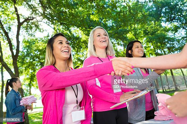 Diverse volunteers helping runners sign up for breast cancer race