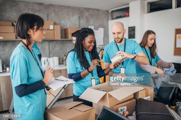 チャリティーフードバンクで募金箱を梱包する多様なボランティア - 非営利団体 ストックフォトと画像