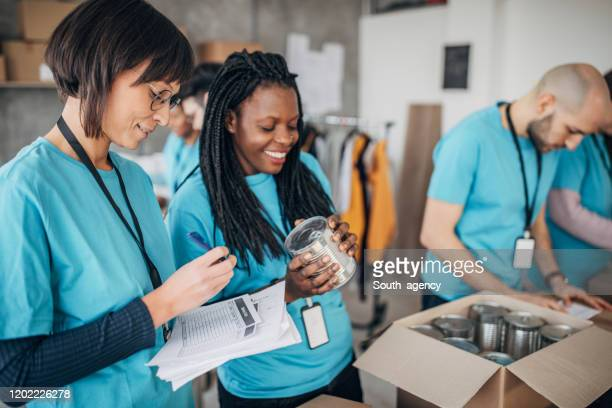 diverse volunteers packing donation boxes in charity food bank - charity and relief work stock pictures, royalty-free photos & images