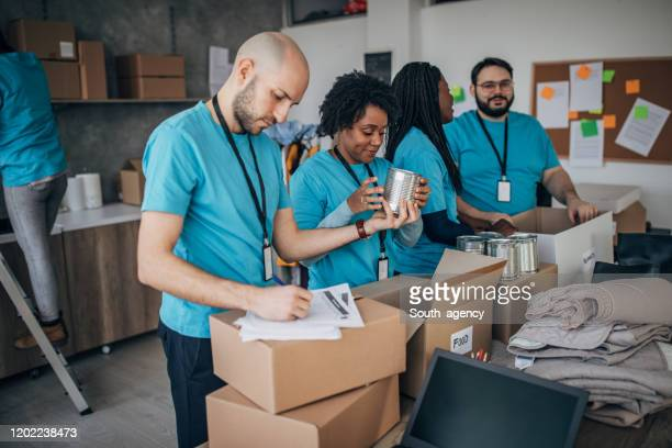 diverse volunteers packing donation boxes in charity food bank - humanitarian aid stock pictures, royalty-free photos & images