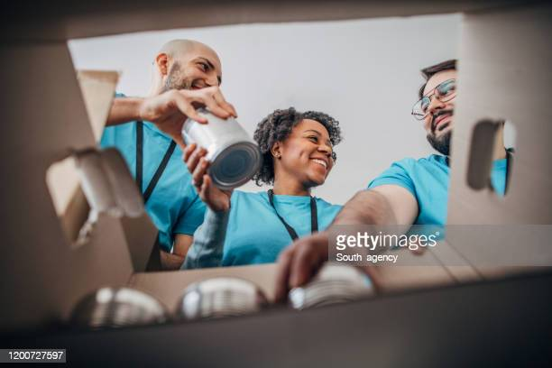 diverse volunteers packing donation boxes with canned food in food bank - charitable donation stock pictures, royalty-free photos & images