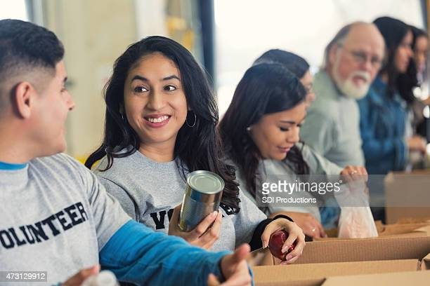 Diverse volunteers sorting food into cardboard boxes for charity