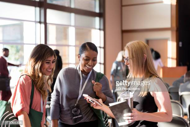 diverse women attending expo smile at smart phone photos - attending stock pictures, royalty-free photos & images