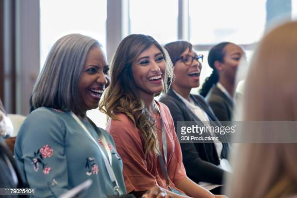 diverse women enjoy laugh during expo session - summit meeting stock pictures, royalty-free photos & images
