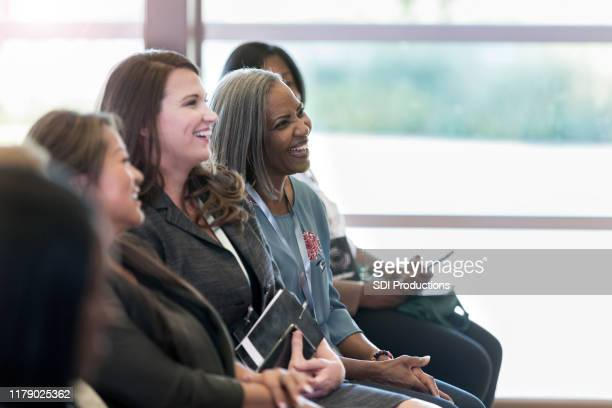 diverse women in front row enjoy comments by unseen presenter - conference centre stock pictures, royalty-free photos & images