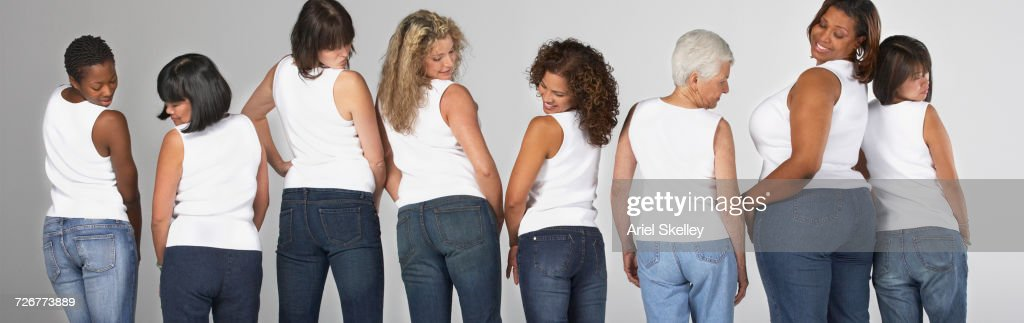 Diverse women looking over shoulders at their buttocks : Stock Photo