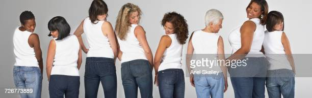 diverse women looking over shoulders at their buttocks - three quarter length stock pictures, royalty-free photos & images